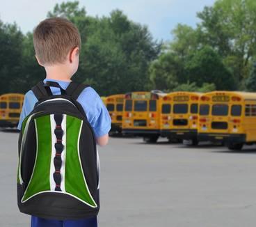 un bambino di spalle con lo zaino di scuola