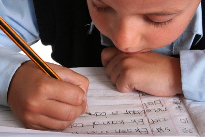 Bambino scrive su un quaderno per disgrafici